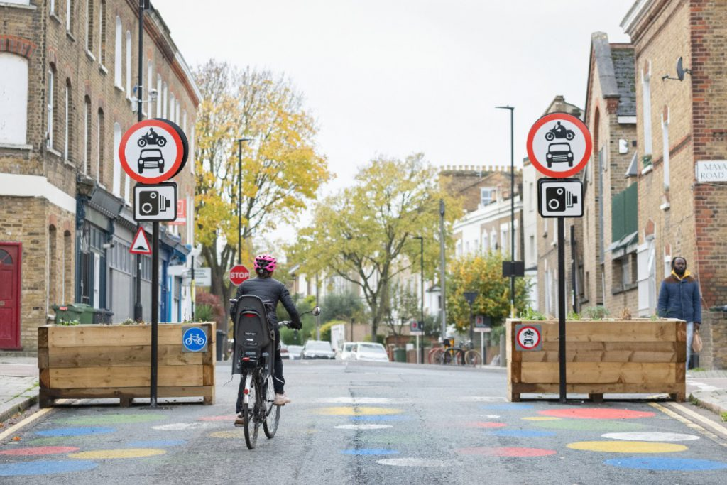 Woman and her child cycling past Low Traffic Neighbourhood signs.