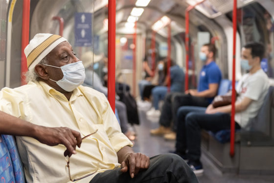 Man sitting on a Tube carriage wearing a face covering