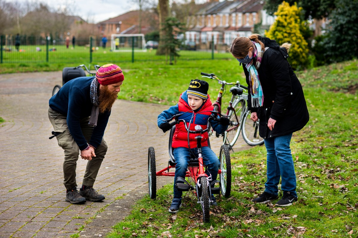 Boy learning to cycle independently on an adapted cycle