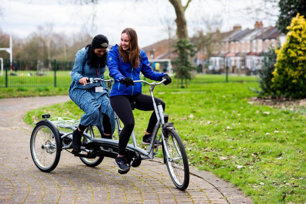 Girls laughing on a tandem cycle