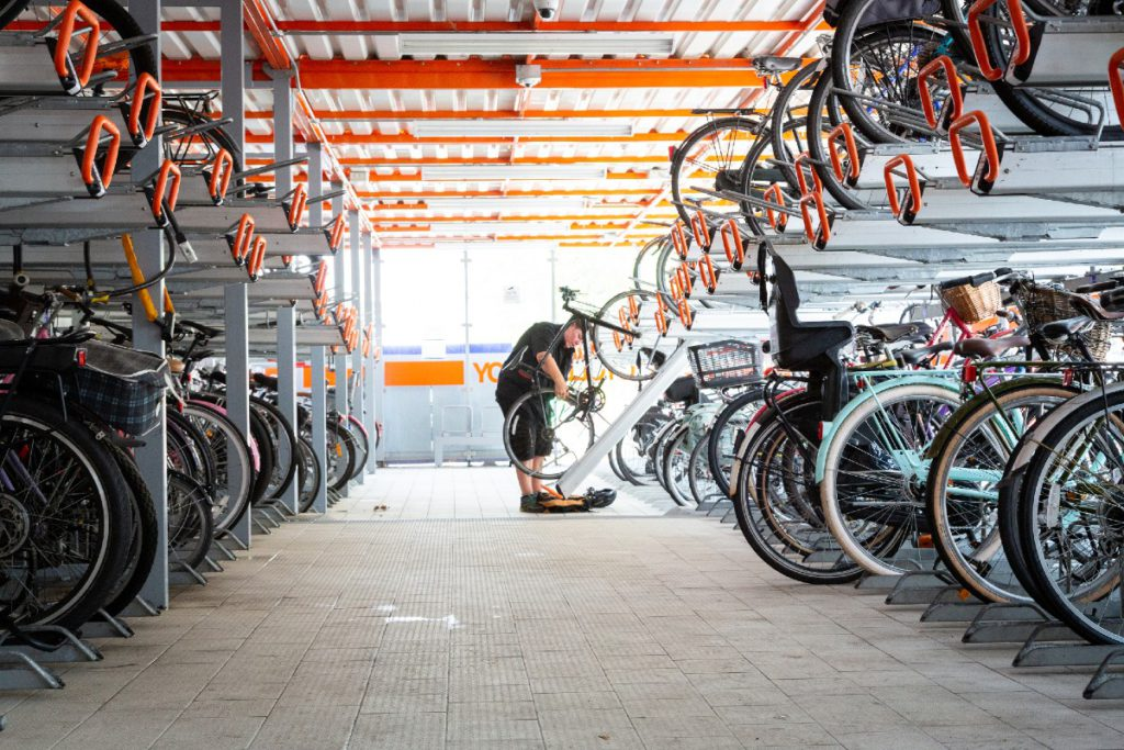 Woman parking her cycling next to other cycles in a cycle hangar