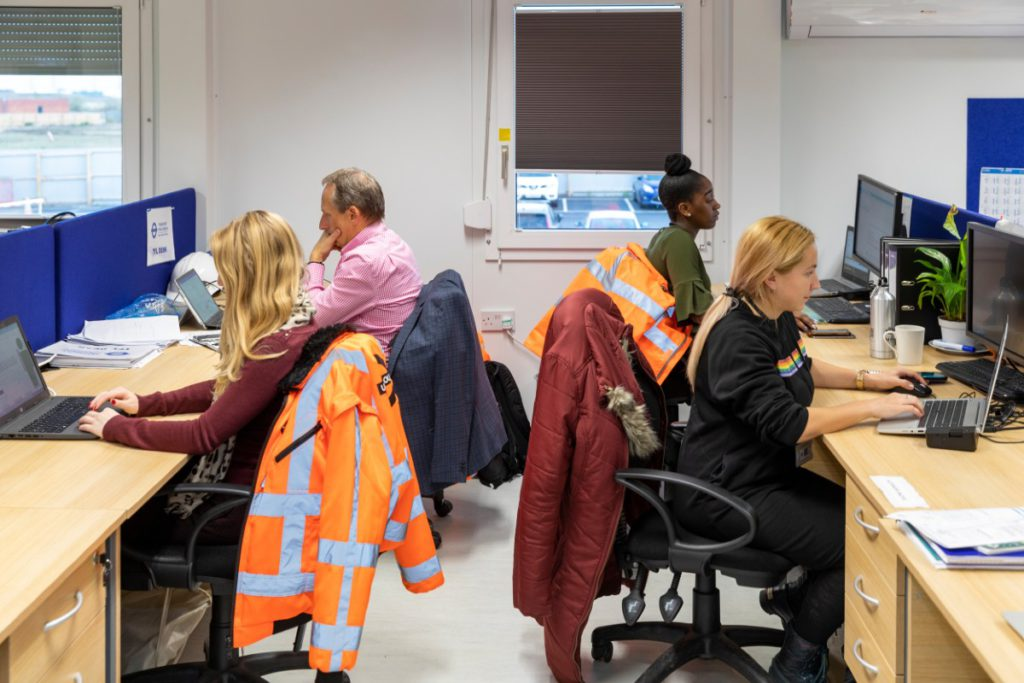 Women working at desks for the construction skills course at the Barking Riverside extension building site