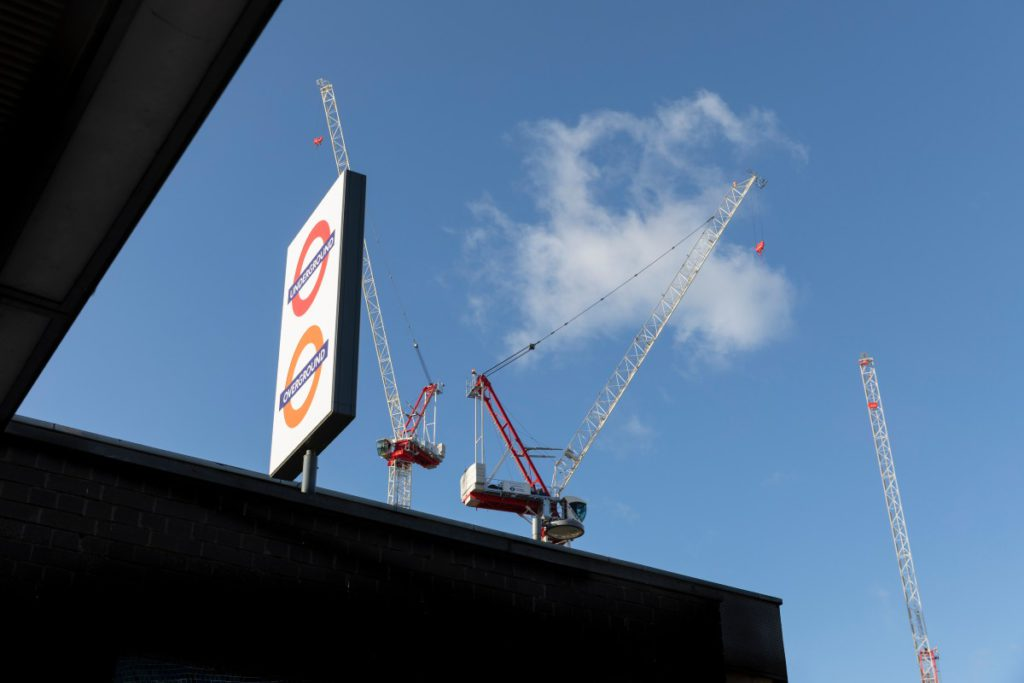 Cranes in the sky behind a station